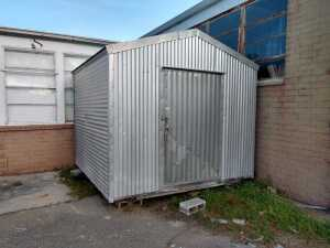 BEHIND KITCHEN, 10 X 10 ALUMINUM CORRUGATED METAL WITH WOOD FRAME SHED, SITTING ON BLOCKS