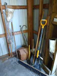 INSIDE BARN, MISCELLANEOUS GARDEN TOOLS TO INCLUDE PITCHFORK AND TWO SHOVELS IN FLOOR MOP TYPE BROOM