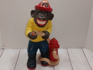 FIRE DEPARTMENT THEMED PLASTER MONKEY HOLDING A HOSE ATTACHED TO A HYDRANT