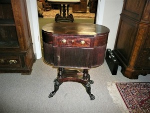 ANTIQUE MAHOGANY 1830S SEWING STAND WITH TAMBOUR DOOR RESTING ON ACANTHUS ADORNED LEGS WITH CARVED PAW FEET