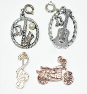 2 STERLING SILVER CHARMS MOTORCYCLE AND MUSIC NOTE ALSO TWO CLIP ON CHARMS GUITAR AND SAX OF UNMARKED METAL