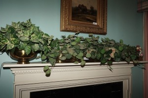 BRASS PLANTERS AND FAUX GREENERY ON FIREPLACE MANTEL - LR