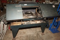 LARGE PORTABLE ROLLING BAND SAW, APPEARS TO BE ABLE TO CUT UP TO APPROXIMATELY FOUR AND A HALF INCH WIDE METAL, DOES POWER UP, IS MOUNTED ON ROLLERS